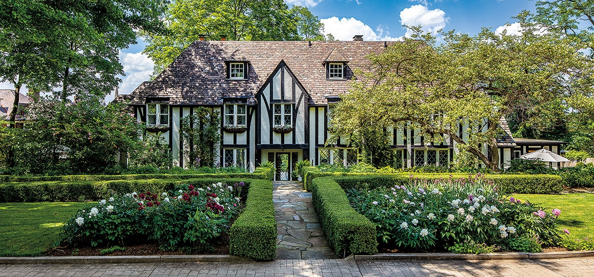 Boxwood, peonies and other seasonal flowers grace the gardens of this charming Tudor-style cottage built in 1925.