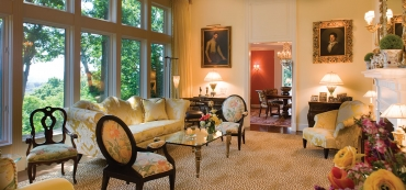 The roof was raised to created a 12-foot ceiling in the living room. A Donghia sofa and chairs are covered in Grey Watkins silk, and Scalamandre silk was used for the window treatments. The leopard carpet by Saxony provides a backdrop for the Louis Mittman table and antique Italian Regency chair. The painting on the left is a 16th-century Italian portrait.