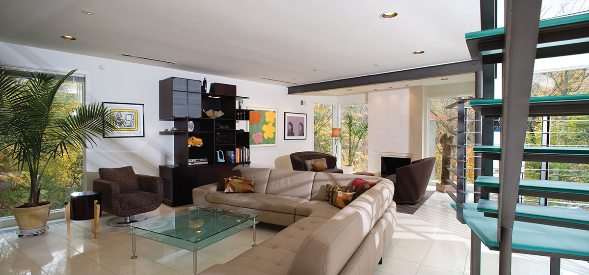 Architect Robert Indovina designed an open main living level with glass walls on the park side of the residence. The family room features a leather sofa from Perlora.