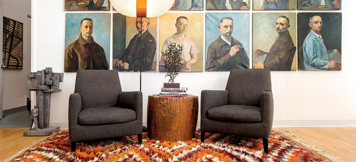 A Noguchi lamp and gray B&B Italia armchairs are placed on a vintage Turkish rug, all from Weisshouse. The haunting series of self portraits painted from the 1950s through the 1970s by an artist named Liptiez anchor the wall in Stacy Weiss' loft and are among her favorite possessions.