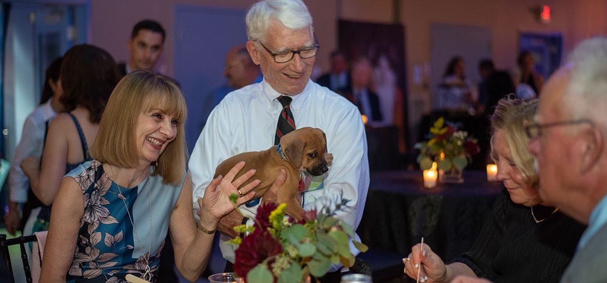 Friday night guests enjoying the company of an adoptable puppy. Animal Friends' Black Tie & Tails. September 20–21, 2019.