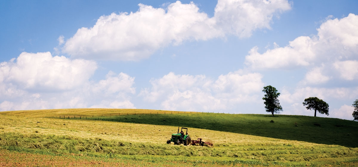 Working the land is still a way of life in Butler County. A tractor rakes mowed hay into rows for drying in the sun before baling.
