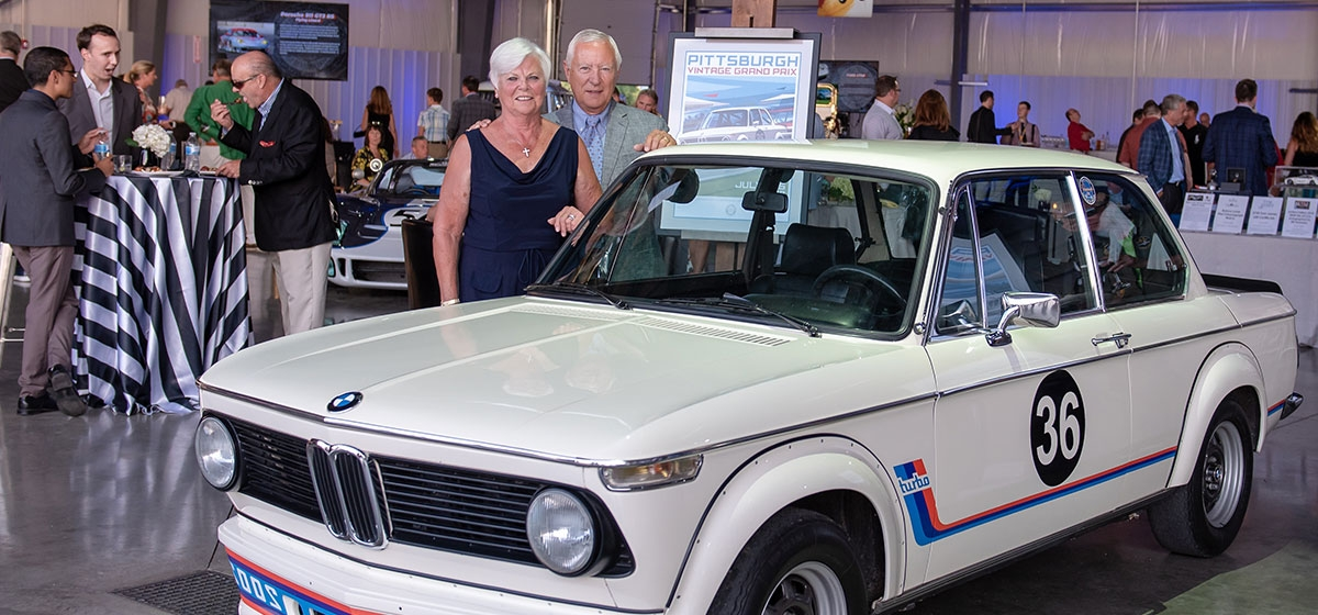 Scott and Fran Hughes of Greenville, SC with their BMW 2002 turbo. Pittsburgh Vintage Grand Prix Passport to Elegance. Voyager Jet Center, Allegheny County Airport. July 12, 2018.
