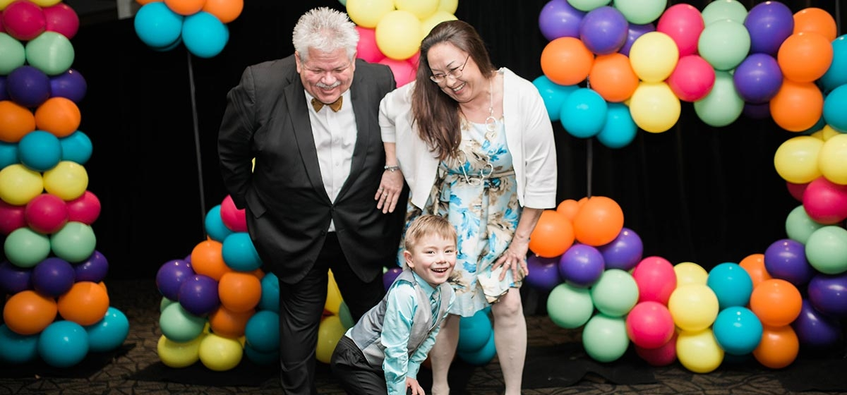 Honorary guests Tina and Jonathan Forehand with special VIP guest, Rick Sebak. Jonathan is a 4-year-old former of the Pediatric Specialty Hospital who recovered from multiple brain tumor surgeries. Shake Your Booties 125th Birthday Party. March 3, 2018.