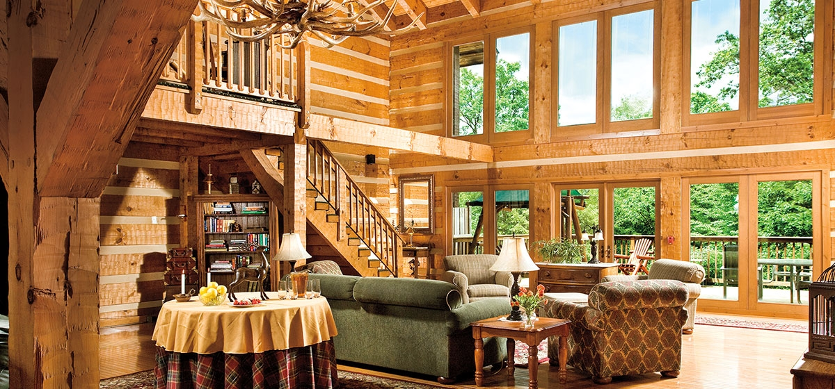 The lodge's Great Room has hewn log beams, a wood-burning hearth, and an outdoor deck surrounded by  forest views.