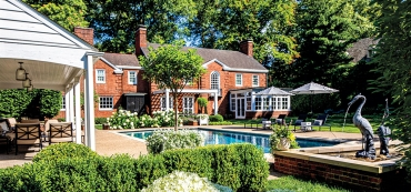 The rear of the Sewickley residence was designed by Kendall O'Brien Landscape Architects, incorporating an existing pool and pool house into the new plan. The lead heron fountain is from Kenneth Lynch.