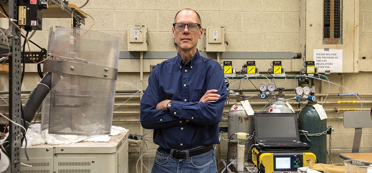 Chris Pistorius, in a lab at Carnegie Mellon University, uses gas tanks, flow controllers, furnace and gas analyzers to mimic conditions in an ironmaking furnace, and measure the response of iron ore to those conditions.