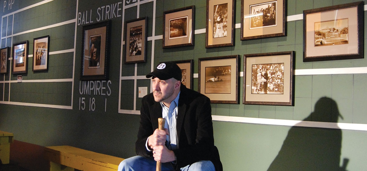 Duane Rieder, photographer and the founder of the Roberto Clemente collection, sits in front of a scoreboard- replica of Forbes Field from the 1960 World Series, lined with photographs of The Great One.