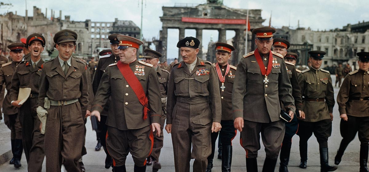 Field Marshal L Montgomery decorates Russian generals at the Brandenburg gate in Berlin, Germany, 12 July 1945. The Deputy Supreme Commander in Chief of the Red Army, Marshal G Zhukov, the Commander of the 21st Army Group, Field Marshal Sir Bernard Montgomery, Marshal K Rokossovsky and General Sokolovsky of the Red Army leave the Brandenburg Gate after the ceremony.