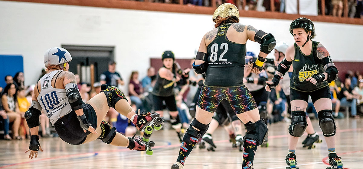 Co-captain Allie Mckill (Jamie Fargo, left) sets up a block to stop a jammer of the Morgantown Vixens.